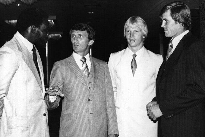 FILE - In this Aug. 29, 1980, file photo, New York Giants coach Ray Perkins, second from left, and players, from left, linebacker Harry Carson, quarterback Phil Simms and linebacker Ray Van Pelt get together in New York for a preseason luncheon. Perkins, who replaced Hall of Famer Bear Bryant as Alabama's football coach and started the transition with the New York Giants that led to two Super Bowl titles, died Wednesday morning, Dec. 9, 2020, in Tuscaloosa. He was 79. The school announced his passing on Wednesday, and daughter Rachael Perkins posted news of his death on her Facebook page. (AP Photo/Ray Howard, File)