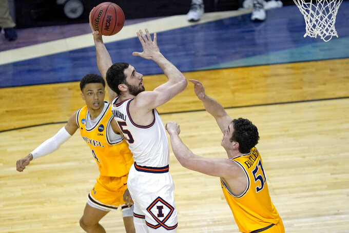 Illinois forward Giorgi Bezhanishvili (15) shoots between Drexel's Xavier Bell, left, and James Butler, during the first half of a first round NCAA college basketball tournament game Friday, March 19, 2021, at the Indiana Farmers Coliseum in Indianapolis .(AP Photo/Charles Rex Arbogast)