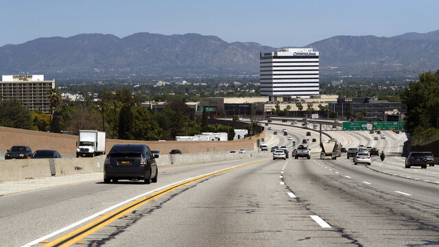 Very light traffic moves north on Interstate 405, into the San Fernando Valley section of Los Angeles on Thursday, April 23, 2020, in Santa Monica, Calif. In the background is the San Gabriel Mountain range now clearly seen due to the very low pollution. (AP Photo/Richard Vogel)