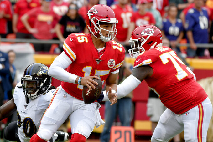Kansas City Chiefs quarterback Patrick Mahomes (15) scrambles as offensive tackle Cam Erving (75) blocks Baltimore Ravens linebacker Pernell McPhee (90) during the first half of an NFL football game in Kansas City, Mo., Sunday, Sept. 22, 2019. (AP Photo/Ed Zurga)