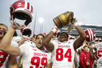 FILE - In this Nov. 30, 2019, file photo, Indiana tight end Turon Ivy Jr. (84) and place kicker Nathanael Snyder (99) celebrate with the Old Oaken Bucket following an NCAA college football game against Purdue in West Lafayette, Ind. The Indiana-Purdue rivalry game has been canceled again. It will be the first time in-state rivals have not met in a football season since the Spanish flu pandemic forced cancellations in 1918 and '19. (AP Photo/Michael Conroy, File)