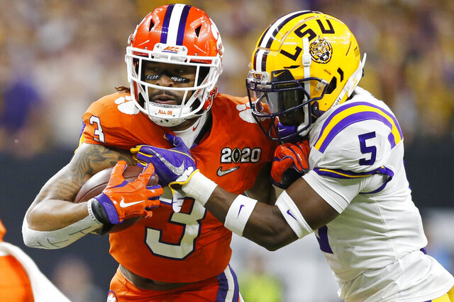 FILE - In this Jan. 13, 2020, file photo, Clemson wide receiver Amari Rodgers, left, is tackled by LSU cornerback Kary Vincent Jr. during the first half of a NCAA College Football Playoff national championship game in New Orleans. All-America wide receiver Ja'Marr Chase, Vincent and defensive end Neil Farrell Jr. have announced they won't be playing this season. (AP Photo/Gerald Herbert, File)