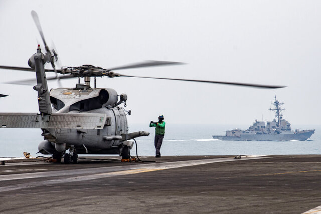 In this photo provided by U.S. Navy, Aviation Electronics Technician 3rd Class James Benzel, from Louisville, Ohio, assigned to the Saberhawks of Helicopter Maritime Strike Squadron, signals an MH-60R Sea Hawk to disengage its rotors on the flight deck of the USS Ronald Reagan (CVN 76) as USS Mustin (DDG 89) steams alongside in South China Sea, Thursday, July 9, 2020. China on Tuesday, July 14, described a U.S. rejection of its maritime claims in the South China Sea as completely unjustified and accused the U.S. of attempting to sow discord between China and the Southeast Asian countries with which it has territorial disputes. (Mass Communication Specialist 3rd Class Erica Bechard/U.S.Navy via AP)