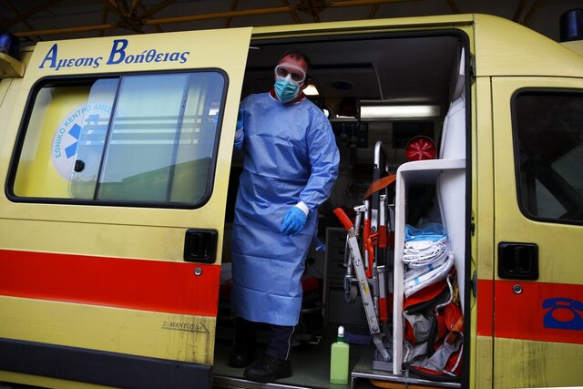A paramedic wearing a suit to protect against coronavirus, closes the door of an ambulance at Evangelismos hospital in Athens, Thursday, Nov. 12, 2020. Greece has imposed a nationwide nightly curfew as the number of COVID-19 cases in the country continues to surge despite a lockdown. (AP Photo/Thanassis Stavrakis)
