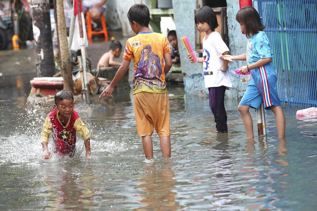 Children play on a flooded street in Jakarta, Indonesia, Sunday, Jan. 5, 2020. Landslides and floods triggered by torrential downpours have left dozens of people dead in and around Indonesia's capital, as rescuers struggled to search for people apparently buried under tons of mud, officials said Saturday. (AP Photo/Tatan Syuflana)