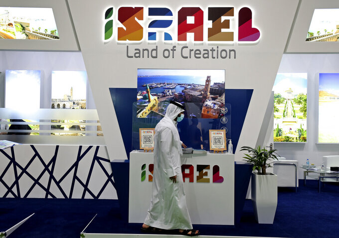 A man passes by the Israel stand on the opening day of the Arabian Travel Market exhibition, in Dubai, United Arab Emirates, Sunday, May 16, 2021. As violence flares within Israel and on a day in which Israeli airstrikes on Gaza City killed at least 42 people Sunday, it was business as usual for a senior Israeli tourism official in Dubai as she promoted the country as a must-see destination for Muslim visitors.  (AP Photo/Kamran Jebreili)