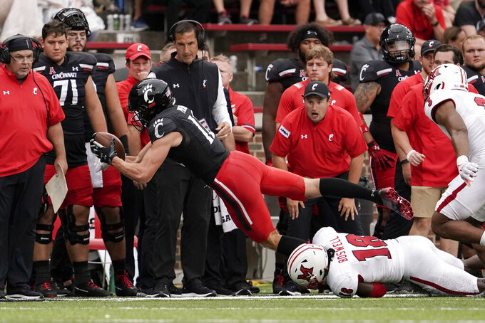 Cincinnati wide receiver Alec Pierce (12) is tackled by Miami (Ohio) defensive back Cedric Boswell (18) during the second half of an NCAA college football game Saturday, Sept. 4, 2021, in Cincinnati. (AP Photo/Jeff Dean)