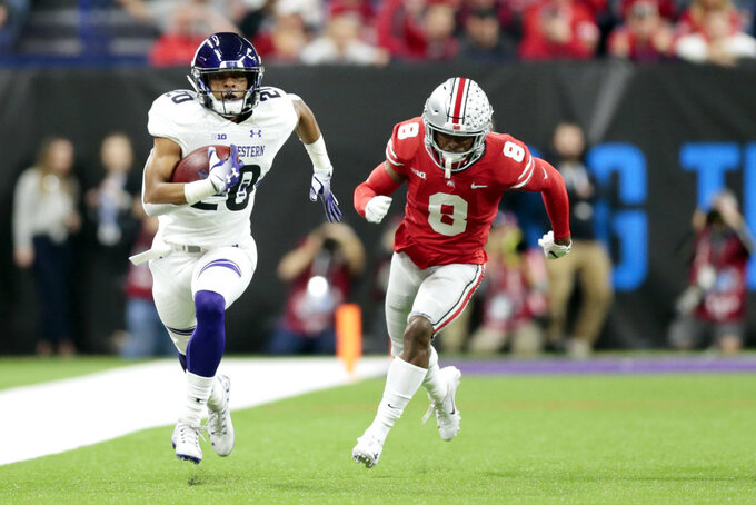 Northwestern running back John Moten IV, left, runs for a touchdown past Ohio State cornerback Kendall Sheffield during the first half of the Big Ten championship NCAA college football game, Saturday, Dec. 1, 2018, in Indianapolis. (AP Photo/AJ Mast)