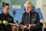 Britain's Prime Minister Boris Johnson listens to apprentice Amy Gray during a visit to a British Gas training academy in Leicestershire, England, Monday, Sept. 13, 2021.(AP Photo/Rui Vieira, Pool)