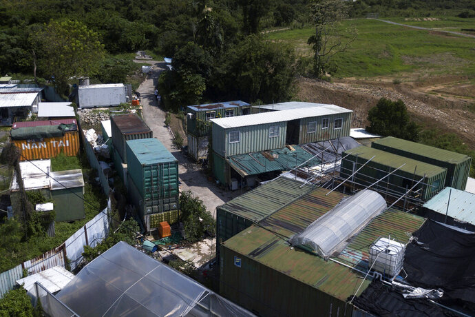 An aerial view of the shipping containers stacked on top of each other at the MoVertical Farm in Yuen Long, Hong Kong's New Territories Tuesday, Sept. 22, 2020. Operating on a rented 1,000 square meter patch of wasteland in the Hong Kong's rural area, Lee's MoVertical Farm utilizes around 30 of the decommissioned containers, to raise red water cress and other local vegetables hydroponically, which eliminates the need for soil. A few are also used as ponds for freshwater fish. (AP Photo/Kin Cheung)