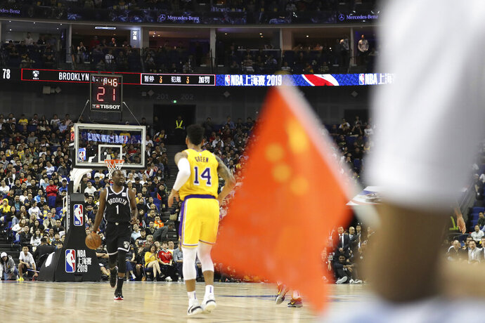 In this Thursday, Oct. 10, 2019, photo, Brooklyn Nets' Theo Pinson, left, drives against Los Angeles Lakers' Danny Green, right, near a Chinese national flag during a preseason NBA game at the Mercedes Benz Arena in Shanghai, China. When Houston Rocket's general manager Daryl Morey tweeted last week in support of anti-government protests in Hong Kong, everything changed for NBA fans in China. A new chant flooded Chinese sports forums: