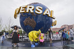 A family wearing raincoats and face masks to help protect themselves from the coronavirus pose for a selfie with an icon near the entrance to the Universal Studios Beijing in Beijing, Monday, Sept. 20, 2021. Thousands of people brave the rain visit to the newest location of the global brand of theme parks which officially opens on Monday. (AP Photo/Andy Wong)