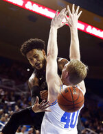 Washington guard David Crisp, left, passes the ball behind UCLA center Thomas Welsh during the first half of an NCAA college basketball game in Los Angeles, Sunday, Dec. 31, 2017. (AP Photo/Ringo H.W. Chiu)