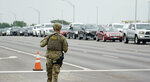 A military policeman walks past traffic outside of a JBSA-Lackland Air Force Base gate, Wednesday, June 9, 2021, in San Antonio. The Air Force was put on lockdown as police and military officials say they searched for two people suspected of shooting into the base from outside. (AP Photo/Eric Gay)