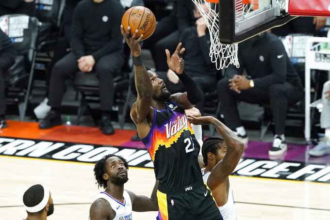 Phoenix Suns center Deandre Ayton, middle, shoots against the Los Angeles Clippers during the first half of Game 2 of the NBA basketball Western Conference Finals, Tuesday, June 22, 2021, in Phoenix. (AP Photo/Matt York)
