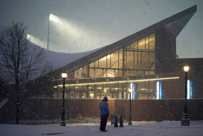 Event worker Toby Miller stands outside the Finneran Pavilion during a winter storm before an NCAA college basketball game between Villanova and Butler, Wednesday, Dec. 16, 2020, in Villanova, Pa. (AP Photo/Matt Slocum)