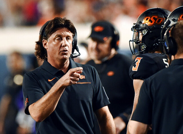 FILE - In this Sept. 28, 2019, file photo, Oklahoma State head coach Mike Gundy points to his staff on the sideline during the first half of an NCAA college football game against Kansas State in Stillwater, Okla. Gundy apologized Saturday, April 11, 2020, for comments this week about the COVID-19 pandemic. (AP Photo/Brody Schmidt, File)