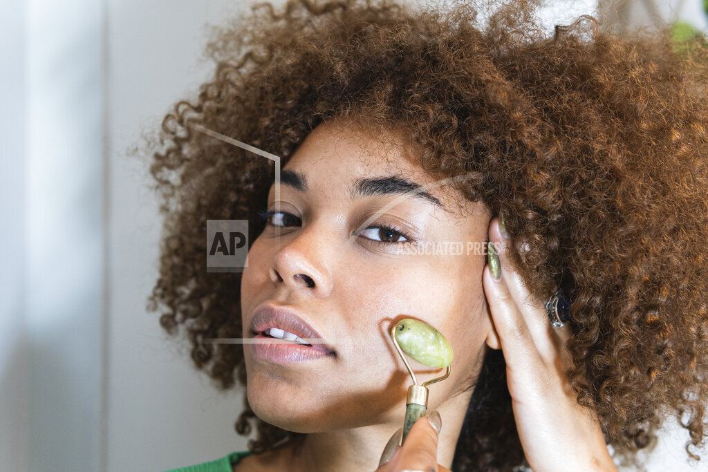 Young woman with hand in hair using jade roller on face