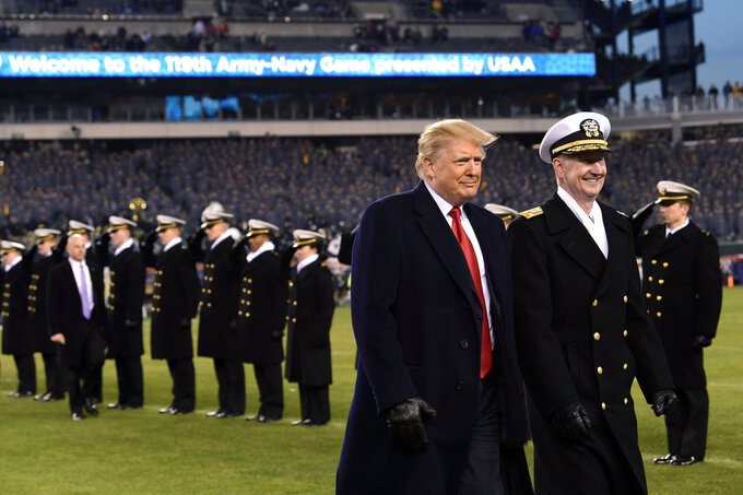 President Donald Trump, center, walks with Naval Academy Superintendent Vice Adm. Ted Carter, right, across the field during half-time at the Army-Navy football game in Philadelphia, Saturday, Dec. 8, 2018. (AP Photo/Susan Walsh)