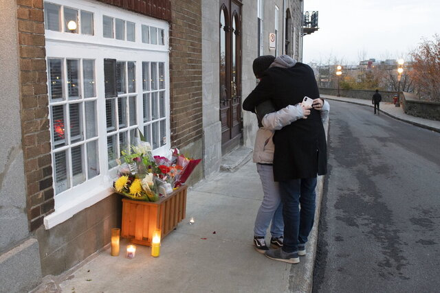 Dimitry Montigny embraces Jessica Peloquin, left, after laying flowers in front of Suzanne Clermont's house in Quebec City, Sunday, Nov. 1, 2020. Clermont was named as one of two people killed Saturday night by a man wielding a sword. Peloquin, who took the 911 call, was in tears. (Jacques Boissinot/The Canadian Press via AP)