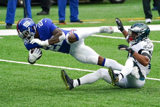 New York Giants' Wayne Gallman (22) jumps over Philadelphia Eagles' Rodney McLeod (23) during the second half of an NFL football game Sunday, Nov. 15, 2020, in East Rutherford, N.J. (AP Photo/Corey Sipkin)