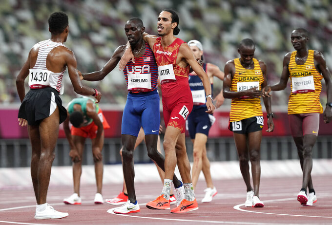Mohamed Katir, of Spain and Paul Chelimo, of United States embrace as they finish in a men's 5,000-meter heat at the 2020 Summer Olympics, Tuesday, Aug. 3, 2021, in Tokyo, Japan. (AP Photo/Martin Meissner)