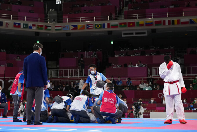 Tareg Hamedi of Saudi Arabia, right, reacts as medical personnel attend to Sajad Ganjzadeh of Iran after he was injured in their men's kumite +75kg gold medal bout for karate at the 2020 Summer Olympics, Saturday, Aug. 7, 2021, in Tokyo, Japan. (AP Photo/Vincent Thian)