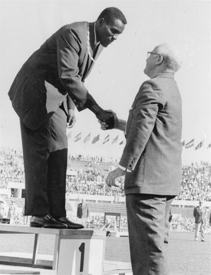 FILE - Rafer Johnson of Kingsburg, Calif., is congratulated by International Olympic Committee President Avery Brundage after presentation of the gold medal for the decathlon event at the Summer Olympics in Rome, Italy, in this Sept., 7, 1960, file photo. Rafer Johnson died Wednesday, Dec. 2, 2020. He was 86. He died at his home in the Sherman Oaks section of Los Angeles, according to family friend Michael Roth  (AP Photo)