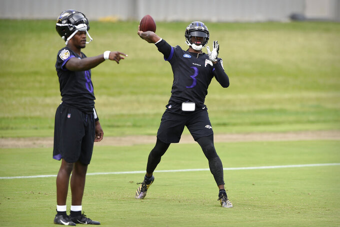 Baltimore Ravens quarterback Robert Griffin III, right, passes as Lamar Jackson points during drills at the team's NFL football training facility in Owings Mills, Md., Wednesday, June 12, 2019 (AP Photo/Gail Burton)