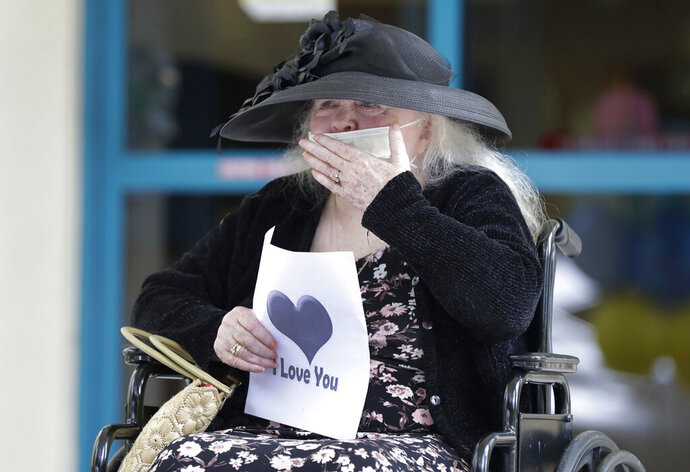 FILE - In this July 17, 2020, file photo, Margaret Choinacki, 87, who has no other family members left because her husband and daughter have died, blows kisses to her friend Frances Reaves during a drive-by visit at Miami Jewish Health in Miami. Floridians will soon be allowed to visit loved ones in nursing homes after nearly six months of vulnerable seniors being cut off from family as Gov. Ron DeSantis announced Tuesday, Sept. 1, 2020, that facilities could start a partial reopening. (AP Photo/Wilfredo Lee, File)