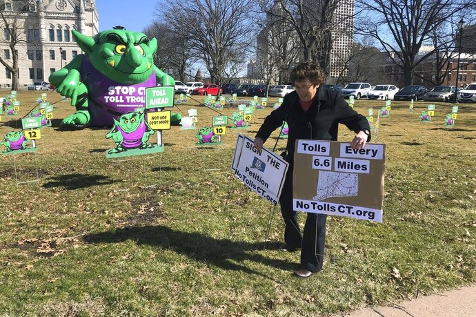 Joanne Baker of Woodstock carries two signs showing her opposition to proposed tolls on Connecticut highways, Tuesday, March 19, 2019, outside the Connecticut State Capitol in Hartford, Conn. The conservative Yankee Institute for Public Policy erected a large