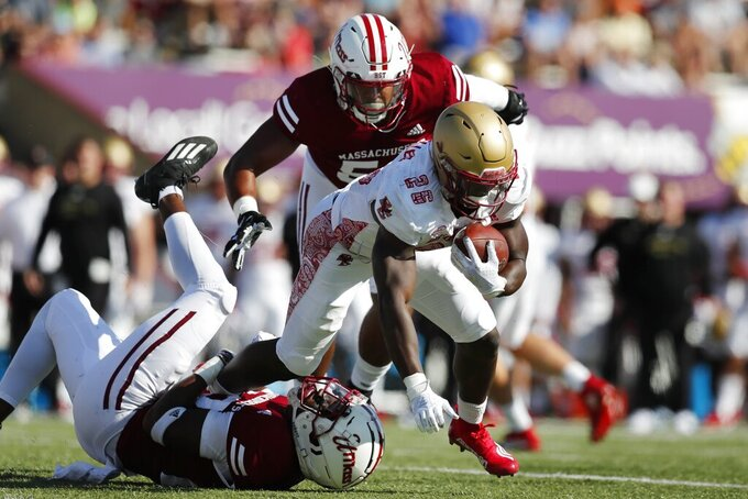 Massachusetts linebacker Gerrell Johnson, bottom, tackles Boston College running back Alec Sinkfield (26) during the first half of an NCAA college football game, Saturday, Sept. 11, 2021, in Amherst, Mass. (AP Photo/Michael Dwyer)