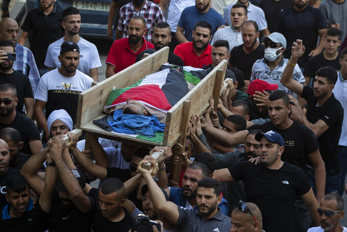 Palestinian mourners carry the body of Raed Jadallah, 39, who was killed by Israeli forces at the western entrance of his village while returning from work in the early hours of Wednesday morning, during his funeral, in the West Bank village of Beit Ur al-Tahta, Wednesday, Sep. 1, 2021. (AP Photo/Majdi Mohammed)