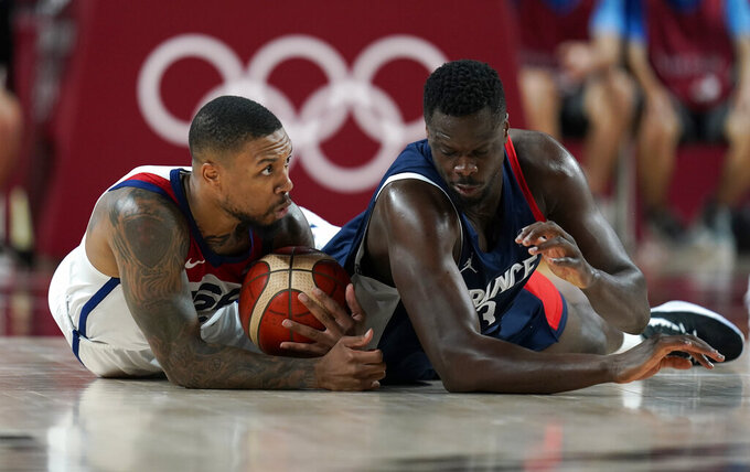 United States' Damian Lillard (6), left, and France's Moustapha Fall (93) fight for a loose ball during men's basketball gold medal game at the 2020 Summer Olympics, Saturday, Aug. 7, 2021, in Saitama, Japan. (AP Photo/Charlie Neibergall)