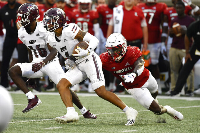 Eastern Kentucky wide receiver Matt Wilcox Jr., center, runs from the grasp of Louisville defensive back Qwynnterrio Cole, right, during the first half of an NCAA college football game in Louisville, Ky., Saturday, Sept. 11, 2021. (AP Photo/Timothy D. Easley)