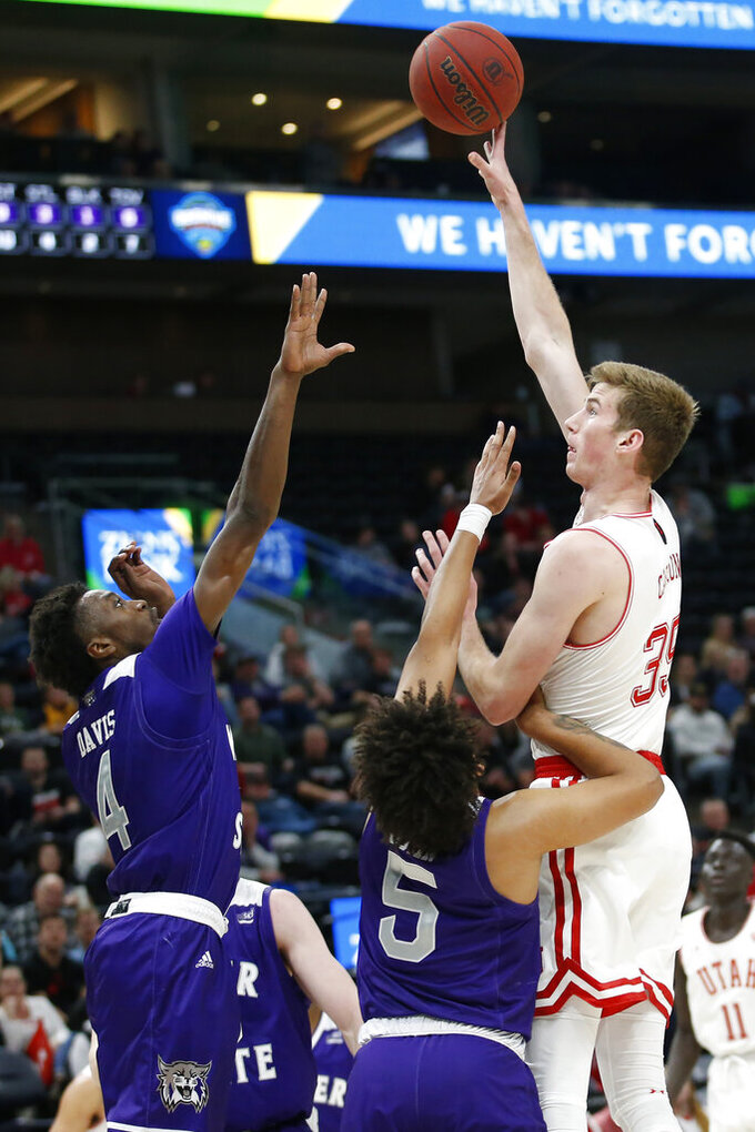 Weber State's Kham Davis (4) and Cody John (5) defend against Utah center Branden Carlson (35) in the second half during an NCAA college basketball game Saturday, Dec. 14, 2019, in Salt Lake City. (AP Photo/Rick Bowmer)