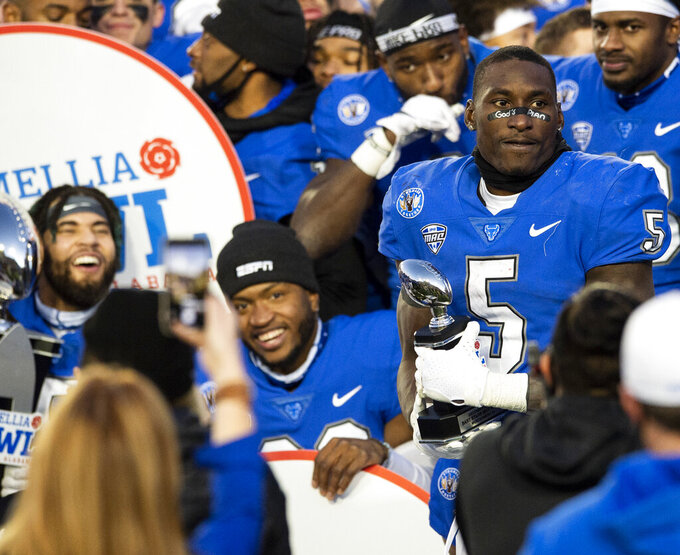Buffalo running back Kevin Marks (5) holds his trophy after being name MVP of the Camellia Bowl NCAA college football game in which Buffalo defeated Marshall 17-10 in Montgomery, Ala., Friday, Dec. 25, 2020. (Jake Crandall/The Montgomery Advertiser via AP)
