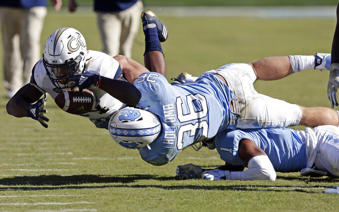 North Carolina's Cole Holcomb (36) tackles Georgia Tech's Jordan Mason (24) during the second half of an NCAA college football game in Chapel Hill, N.C., Saturday, Nov. 3, 2018. Georgia Tech won 38-28. (AP Photo/Gerry Broome)