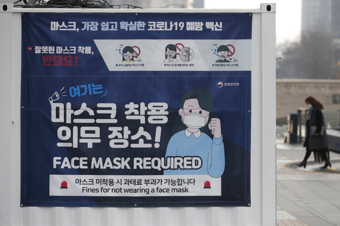 People wearing face masks walk near a banner displaying precautions against the coronavirus in downtown Seoul, South Korea, Monday, Dec. 28, 2020. (AP Photo/Lee Jin-man)