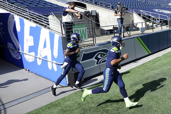 Seattle Seahawks quarterbacks Russell Wilson, right, and Geno Smith, left, run out of the tunnel for warmups before an NFL football game against the Dallas Cowboys, Sunday, Sept. 27, 2020, in Seattle. (AP Photo/Elaine Thompson)