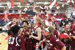 Fordham's Kendell Heremaia (20), Breanna Cavanaugh, center left, and Kaitlyn Downey, left, and the rest of the team celebrate after defeating VCU to win the Atlantic 10 tournament championship NCAA college basketball game, Sunday, March 10, 2019, in Pittsburgh. (AP Photo/Keith Srakocic)