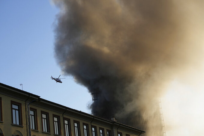 An helicopter flies as smoke billows from a building on fire in Milan, Italy, Sunday, Aug. 29, 2021. (AP Photo/Luca Bruno)