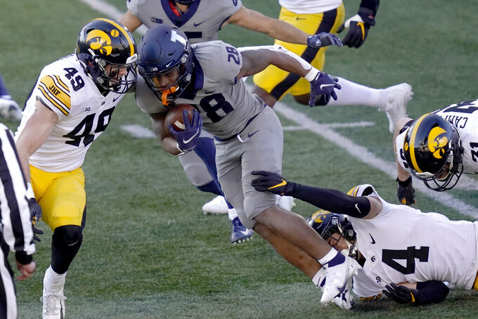 Illinois running back Reggie Love III (28) carries the ball as Iowa linebacker Nick Niemann defends during the first half of an NCAA college football game Saturday, Dec. 5, 2020, in Champaign, Ill. (AP Photo/Charles Rex Arbogast)