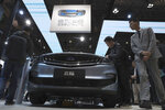 FILE - In this April 16, 2019, file photo, visitors take a close look at a latest car from Chinese automaker Geely Auto during the Auto Shanghai 2019 show in Shanghai. Chinese automaker Geely said Monday, Jan. 11, 2021, it will form an electric car venture with tech giant Baidu, adding to a flurry of corporate tie-ups in the industry to share soaring technology development costs. (AP Photo/Ng Han Guan, File)