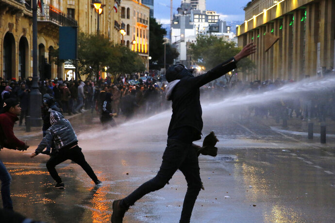 Anti-government protesters throw stones at the riot police during ongoing protests in Beirut, Lebanon, Wednesday, Jan. 22, 2020.  Lebanon's new government has held its first meeting a day after it was formed following a three-month political vacuum. (AP Photo/Bilal Hussein)