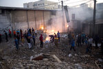 Palestinians check the dame of buildings destroyed by Israeli airstrikes early morning in Gaza City, Saturday, Oct. 27, 2018. Israeli aircraft have struck dozens of militant sites across the Gaza Strip as militants fired some 30 rockets into Israel. (AP Photo/Khalil Hamra)