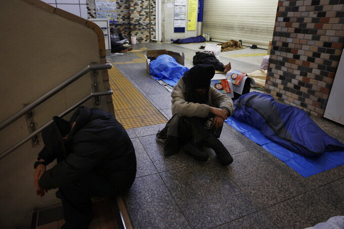 FILE - In this Jan. 9, 2020, file photo, homeless people sleep on the concrete floor of Shinjuku Station, in Tokyo. A group representing the homeless is asking to use the Athletes Village for next year's Tokyo Olympics as a shelter during the coronavirus pandemic. An online petition addressed to Tokyo Olympic organizers and the city government has drawn ten of thousands of signatures for permission to occupy the massive housing complex going up alongside Tokyo Bay. (AP Photo/Jae C. Hong, File)