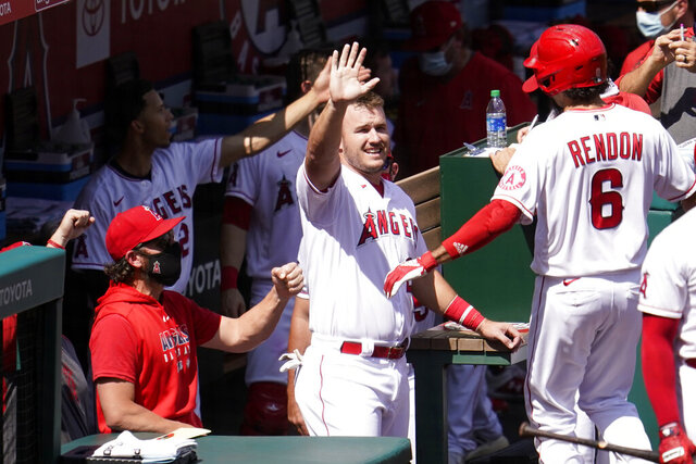 Los Angeles Angels' Anthony Rendon, right, celebrates his two-run home run with Mike Trout, center, during the first inning of a baseball game against the Arizona Diamondbacks, Thursday, Sept. 17, 2020, in Anaheim, Calif. (AP Photo/Marcio Jose Sanchez)