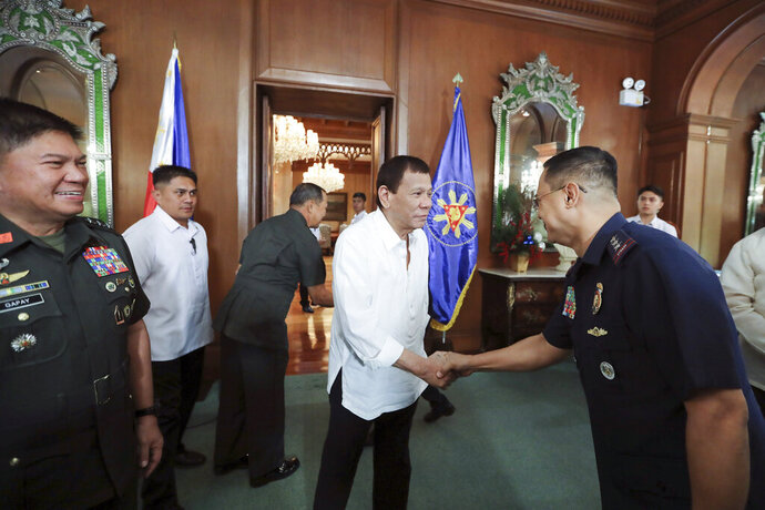 In this Jan. 5, 2020, handout photo provided by the Malacanang Presidential Photographers Division, Philippine President Rodrigo Duterte, center, greets security officials at the Malacanang presidential palace in Manila, Philippines. Duterte has ordered the military to prepare to deploy its aircraft and ships