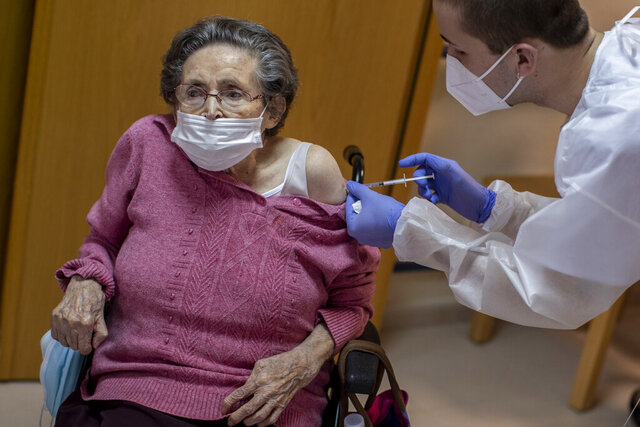 A nurse administers the Pfizer-BioNTech COVID-19 vaccine to a resident at DomusVi nursing home in Alcala Henares, Spain, Thursday, Jan. 28, 2021. Health authorities in Spain are complaining that they are running short of COVID-19 vaccines due to delays in deliveries by pharmaceutical companies. Spain along with the rest of the European Union has suffered delays since Pfizer announced two weeks ago that it would reduce deliveries temporarily during a plant upgrade. (AP Photo/Manu Fernandez)